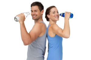 Portrait of a happy fit young couple with water bottles over whi